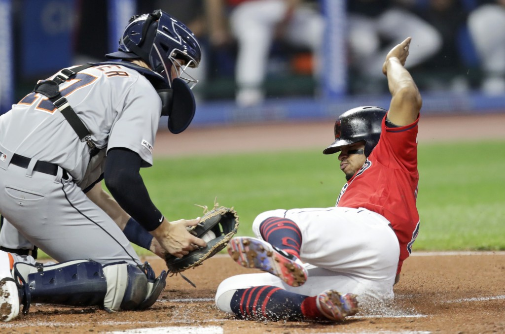 Cleveland Indians' Francisco Lindor, right, scores ahead of the tag from Detroit Tigers catcher Grayson Greiner in the first inning in a baseball game...