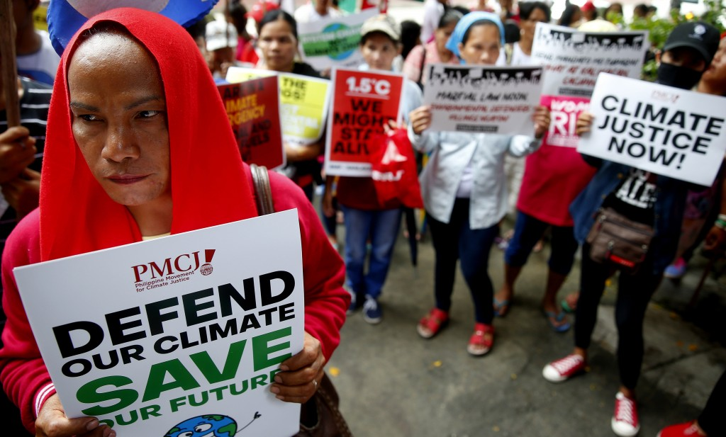 Environmental activists hold placards during a rally outside the Department of Environment and Natural Resources to coincide with the global protests ...
