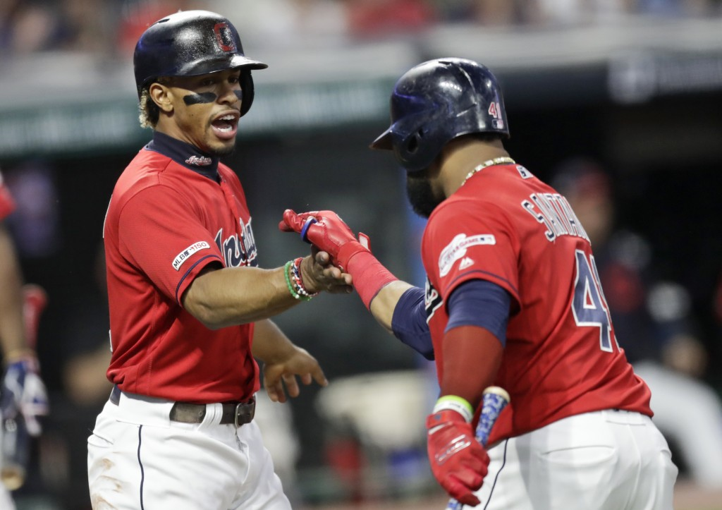 Cleveland Indians' Francisco Lindor, left, congratulates Carlos Santana after Santana hit a sacrifice fly in the first inning in a baseball game again...