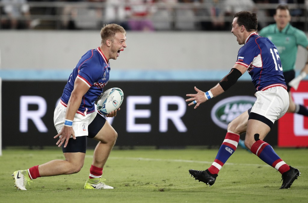 Russia's Kirill Golosnitskiy, left, celebrates with teammate Vasily Artemyev after scoring a try during the Rugby World Cup Pool A game at Tokyo Stadi...