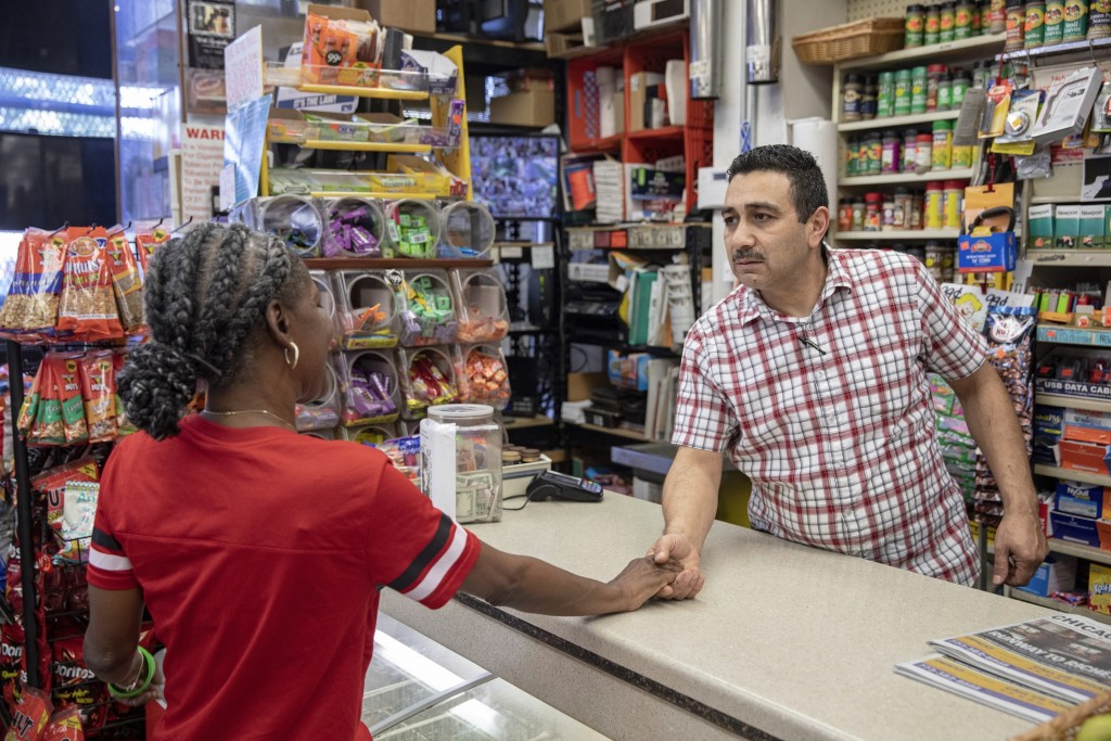 In this Monday, Aug. 19, 2019, photo, Sami Deffala, owner of the Morgan Mini Mart in Chicago's Englewood neighborhood, right, offers his condolences t...