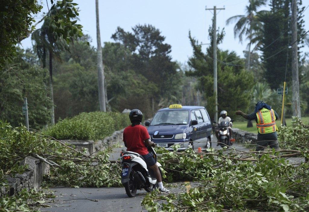 A city worker directs traffic away from trees felled by Hurricane Humberto, in the Devonshire parish of Bermuda, Thursday, Sept. 19, 2019. Humberto bl