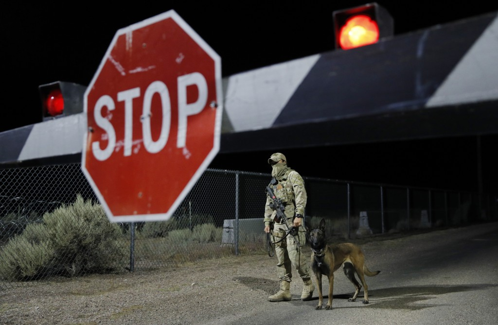 A security guard stands at an entrance to the Nevada Test and Training Range near Area 51 Friday, Sept. 20, 2019, near Rachel, Nev. People gathered at...