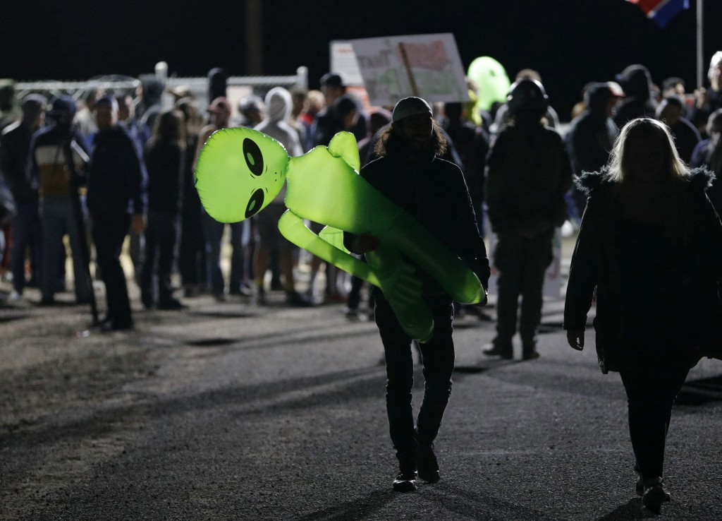 A mans holds an inflatable alien at an entrance to the Nevada Test and Training Range near Area 51 Friday, Sept. 20, 2019, near Rachel, Nev. People ga