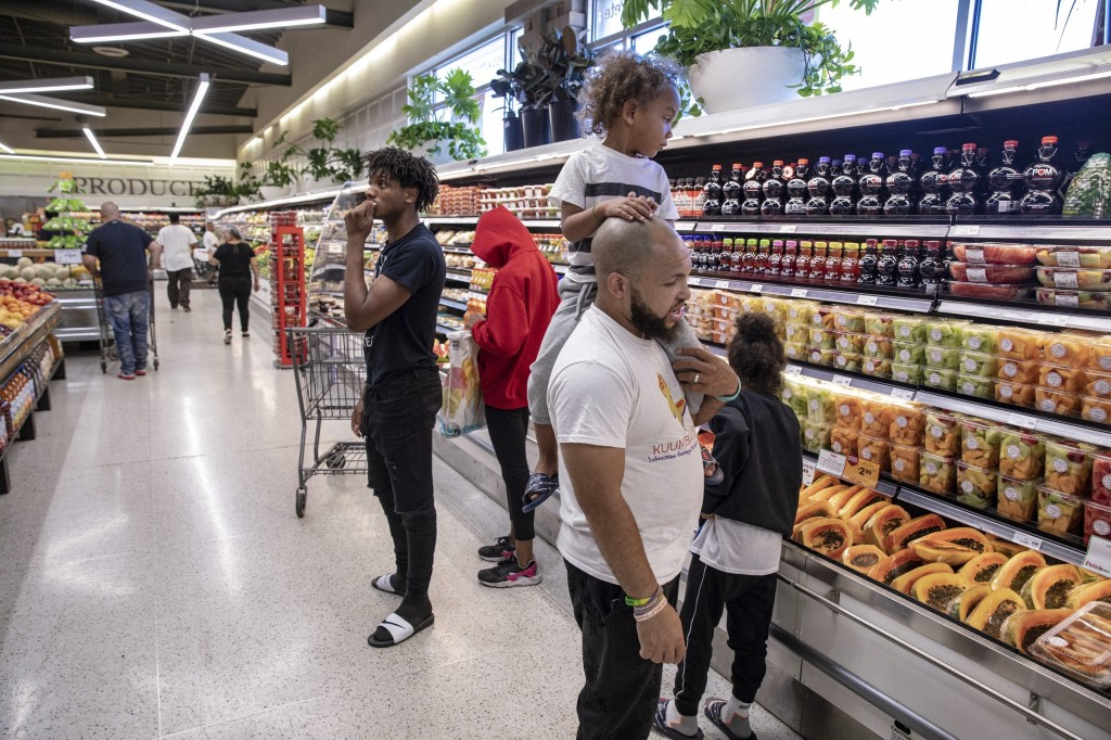 """In this Thursday, Aug. 15, 2019, photo, Christopher """"Mad Dog"""" Thomas, carries his son, Rian Gatewood-Hillestad, while shopping at Pete's Market in Chi"""