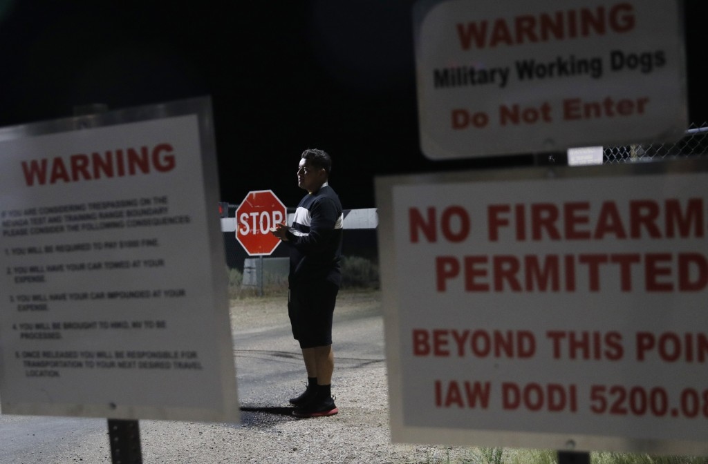 A man stands at an entrance to the Nevada Test and Training Range near Area 51 Friday, Sept. 20, 2019, near Rachel, Nev. People gathered at the gate i...