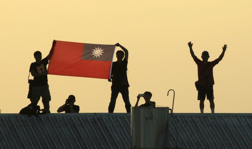 FILE - In this Sept. 14, 2014, file photo, locals on a warehouse rooftop display the national flag while watching Taiwan fighter jets practice during