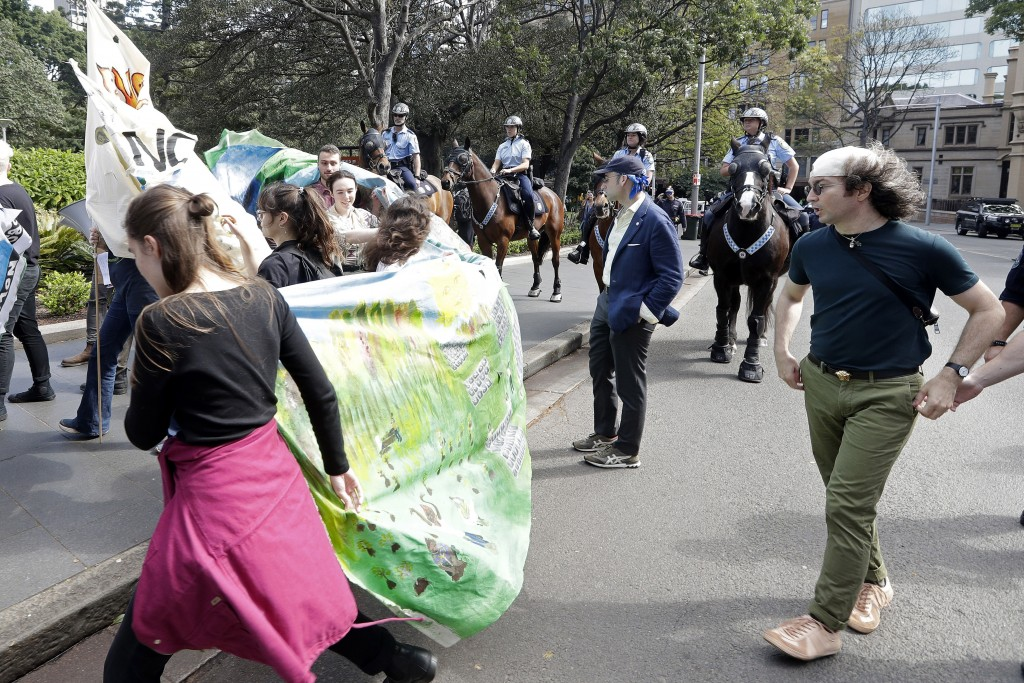 Mounted police block a path as thousands of protestors, many of them school students, attempt to march on the streets in Sydney, Friday, Sept. 20, 201