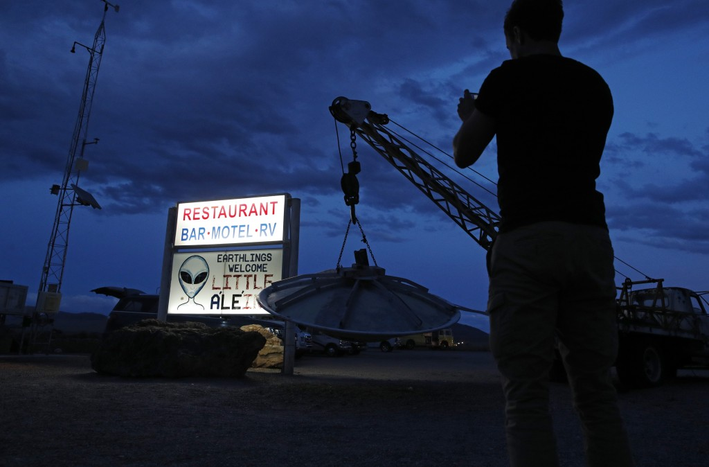 """A man takes a picture of a sign at the Little A'Le'Inn during an event inspired by the """"Storm Area 51"""" internet hoax, Thursday, Sept. 19, 2019, in Rac..."""