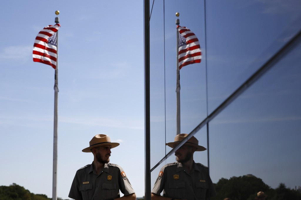 A National Park Service park ranger is reflected in the glass wall of a new security screening building at the foot of the Washington Monument followi...