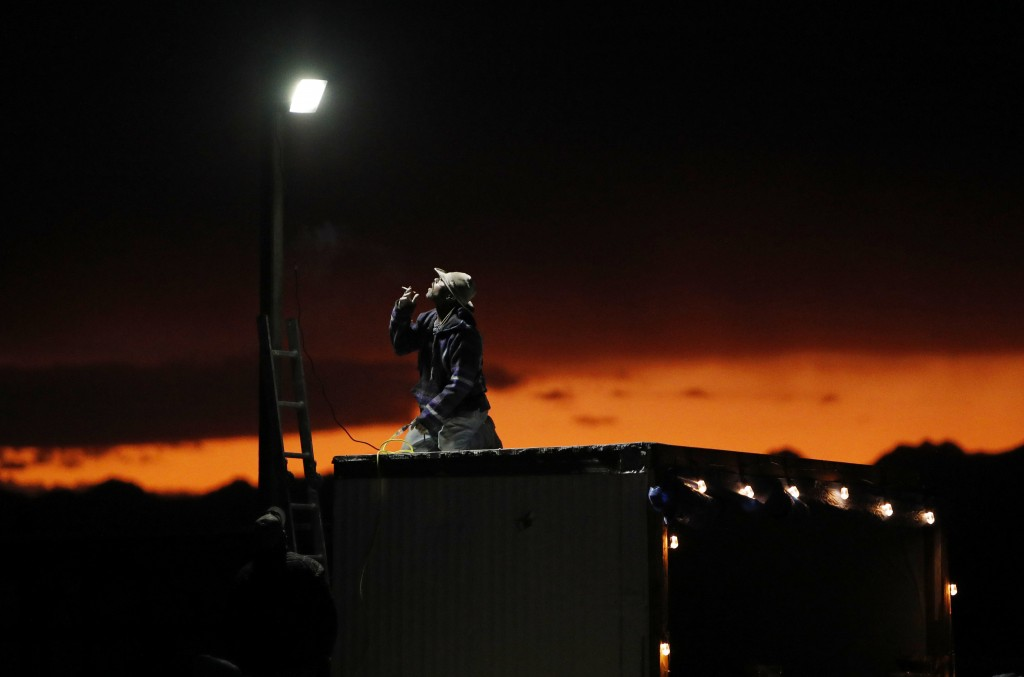 """A man sets up a a light in preparation for an event inspired by the """"Storm Area 51"""" internet hoax near the Little A'Le'Inn motel and cafe, Thursday, S"""
