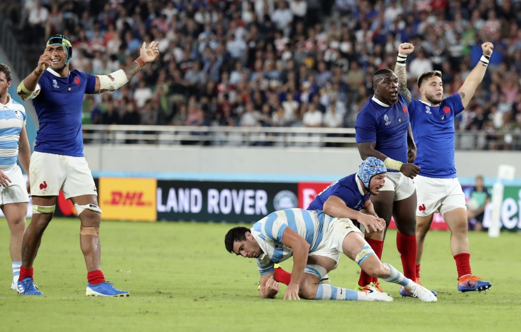 French players celebrate after teammate Camille Lopez kicked a drop goal during the Rugby World Cup Pool C game at Tokyo Stadium between France and Ar...