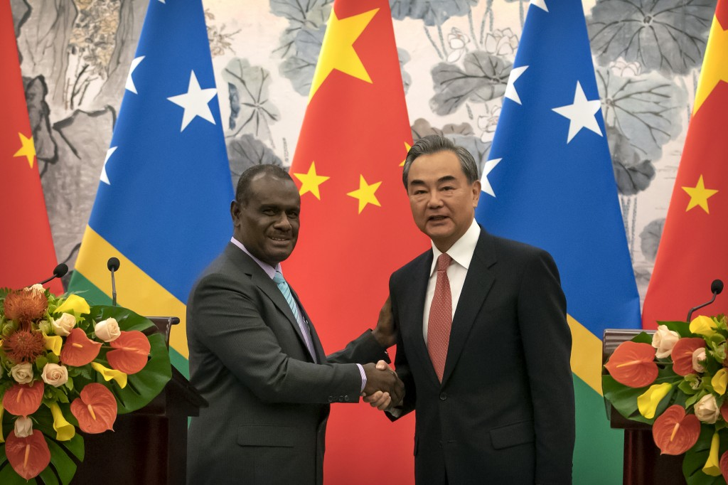Solomon Islands Foreign Minister Jeremiah Manele, left, and Chinese Foreign Minister Wang Yi shake hands at a ceremony to mark the establishment of di...