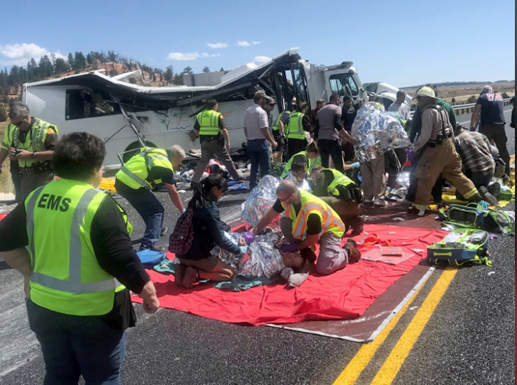 In this photo released by the Garfield County Sheriff's Office, Emergency Medical Services personnel assist victims of a bus crash near Bryce Canyon N...