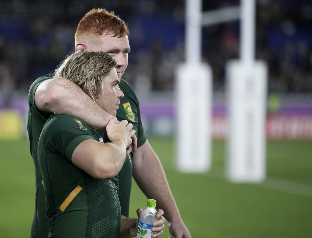 South Africa's Faf de Klerk is embraced by teammate Steven Kitshoff following their Rugby World Cup Pool B game at International Stadium between New Z...