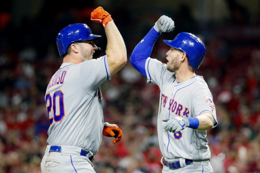 New York Mets' Pete Alonso, left, celebrates with Jeff McNeil, right, after hitting a two-run home run off Cincinnati Reds starting pitcher Sal Romano...
