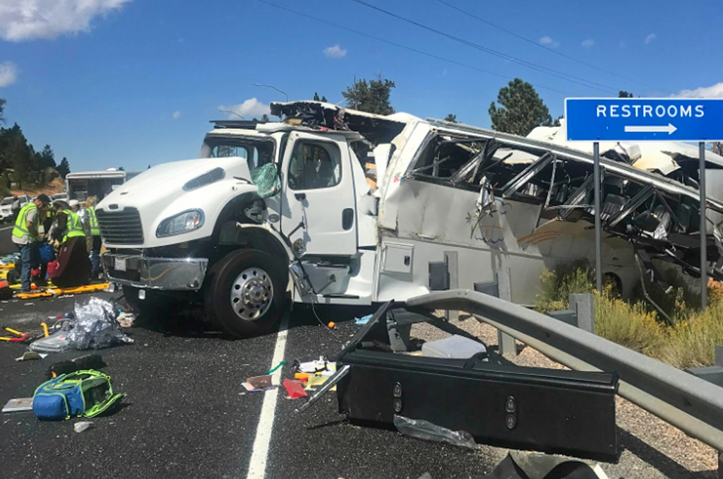 This photo released by the Garfield County Sheriff's Office shows a tour bus that was carrying Chinese-speaking tourists after it crashed near Bryce C...