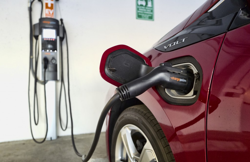 FILE - This Wednesday, Oct. 17, 2018  file photo shows a Chevrolet Volt hybrid car charging at a ChargePoint charging station at a parking garage in L...