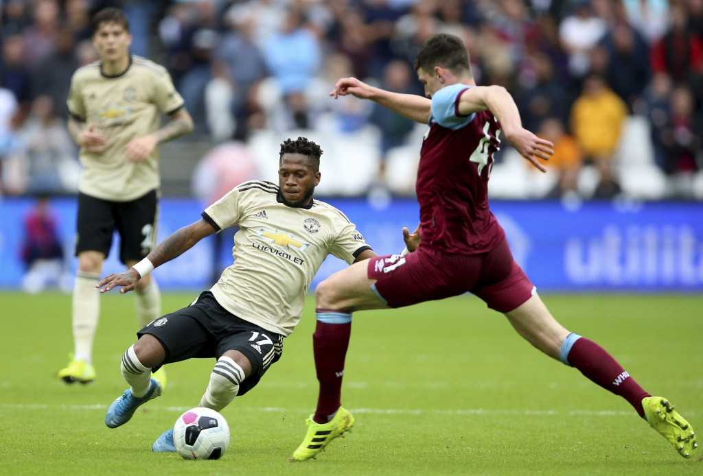Manchester United's Fred, left, slides in on West Ham United's Declan Rice during the English Premier League soccer match at London Stadium, Sunday Se...
