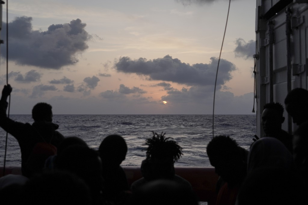 Migrants are silhouetted during the sunrise on the deck of the Ocean Viking as it sails in the Mediterranean Sea, Saturday, Sept. 21, 2019. The humani...