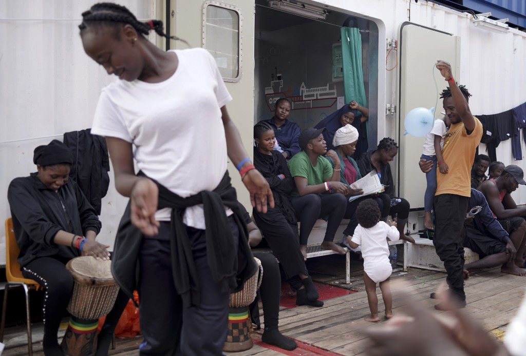 Rescued migrants dance and sing on the deck of the Ocean Viking as it sails in the Mediterranean Sea, Saturday, Sept. 21, 2019. The humanitarian ship ...