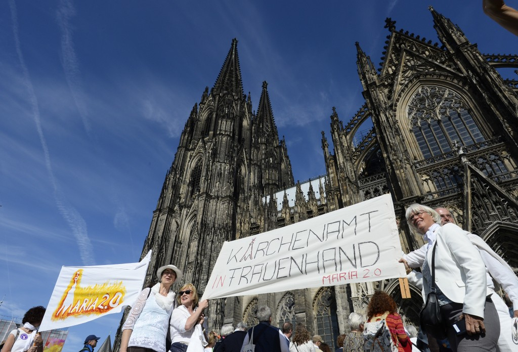 Protesters build a human chain in front of the Cologne Cathedral in Cologne, Germany, Sunday, Sept. 22, 2019. About 800 people have protested for more