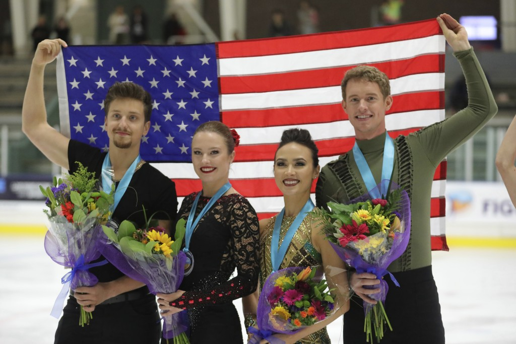 First-place finishers Madison Chock and Evan Bates, right, celebrates with Christina Carreira and Anthony Ponomarenko, left, both of the United States...