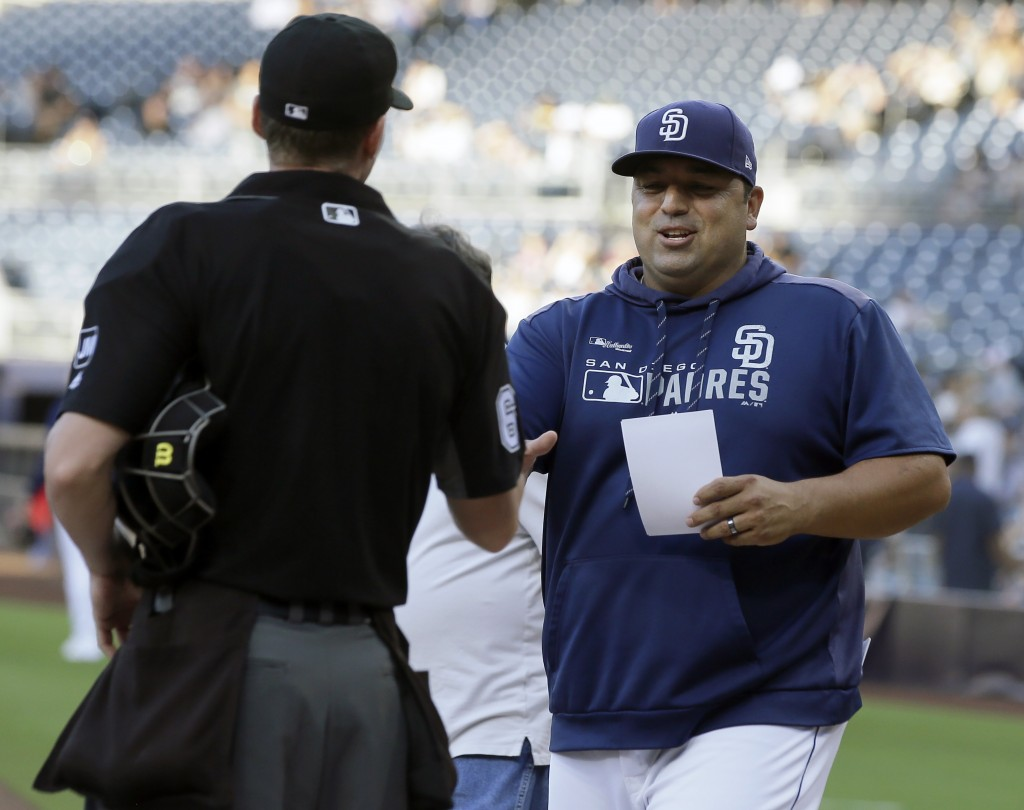 San Diego Padres interim manager Rod Barajas, right, meets with home plate umpire Alex Tosi before a baseball game against the Arizona Diamondbacks in