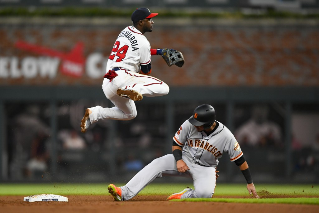 Atlanta Braves second baseman Adeiny Hechavarria (24) throws above San Francisco Giants' Cristhian Adames after forcing him out at second base for a d