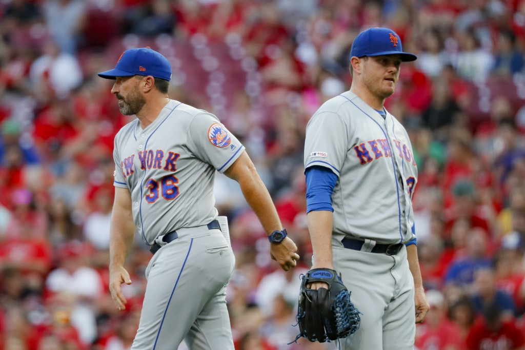 New York Mets manager Mickey Callaway (36) relieves relief pitcher Justin Wilson, right, in the eighth inning of a baseball game against the Cincinnat...