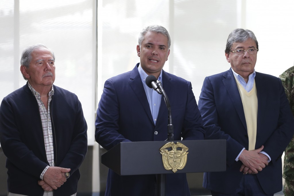 Flanked by Defense Minister Guillermo Boterto, left, and Minister of Foreign Affairs Carlos Holmes Trujillo, Colombia's President Ivan Duque delivers ...