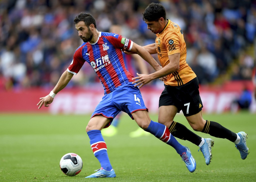 Crystal Palace's Luka Milivojevic, left, and Wolverhampton Wanderers' Pedro Neto battle for the ball during the English Premier League soccer match at...