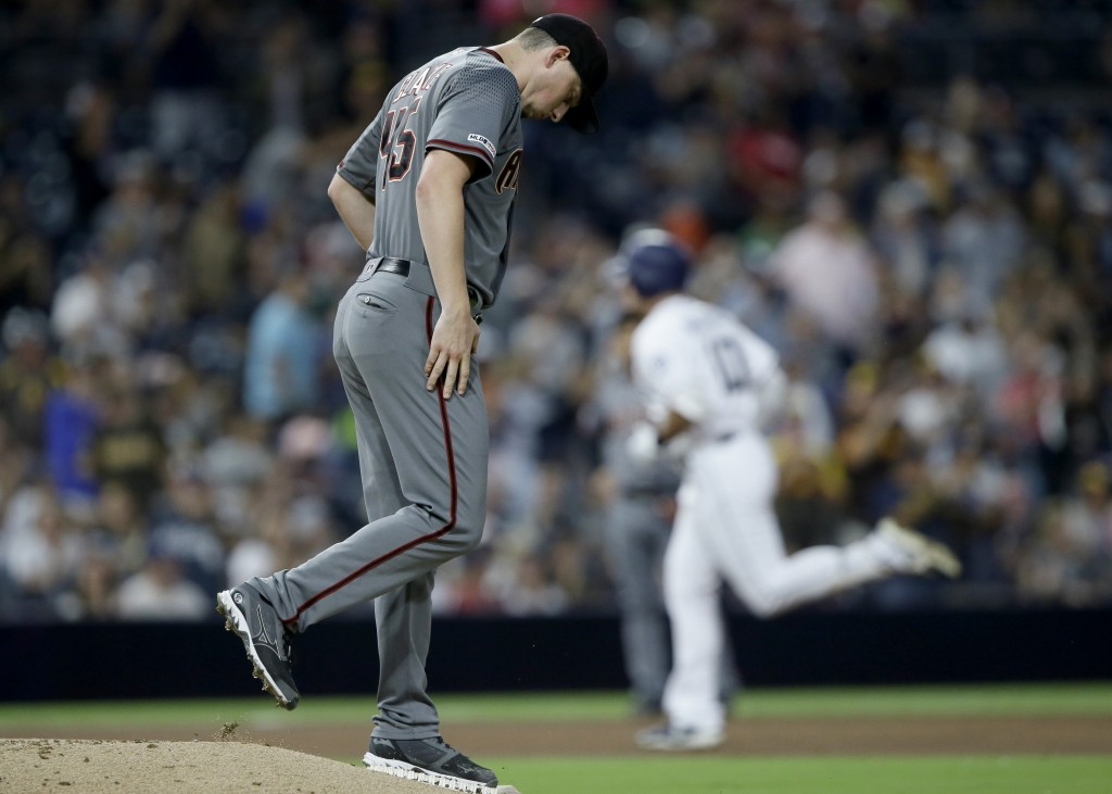 Arizona Diamondbacks starting pitcher Taylor Clarke gathers himself on the mound as San Diego Padres' Hunter Renfroe rounds third after hitting a solo