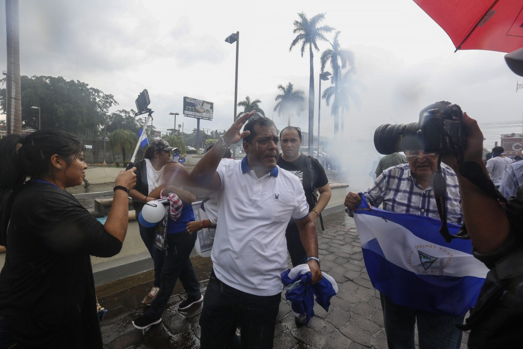 """People turn away as police launch tear gas to disperse demonstrators at an anti-government march dubbed, """"Nothing is Normal"""" in honor of slain student..."""