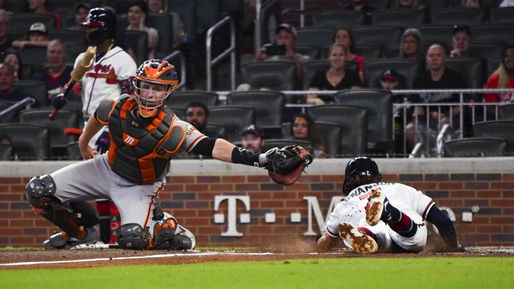 Atlanta Braves' Dansby Swanson scores as San Francisco Giants catcher Buster Posey reaches after a throw from first base during the second inning of a