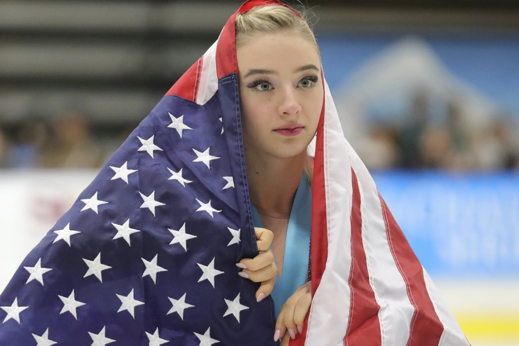 Flag-draped Amber Glenn, of the United States, skates around the rink after her third-place finish at the U.S. International Figure Skating Classic on...