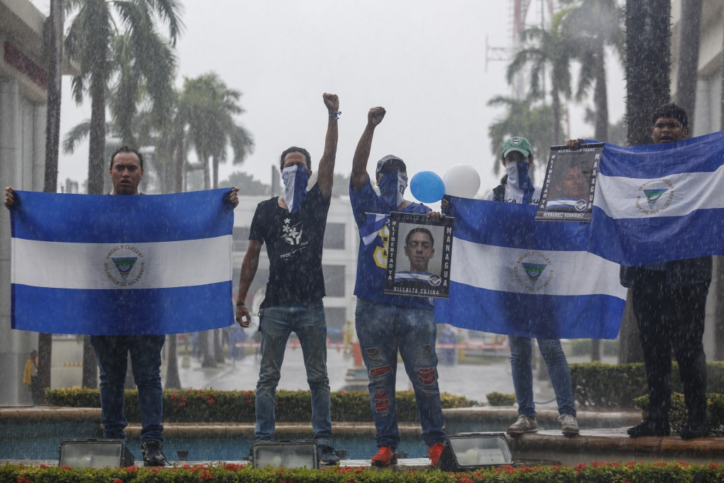 """Demonstrators hold Nicaraguan national flags and photos of a slain students, during an anti-government march dubbed, """"Nothing is Normal"""" in honor of M..."""