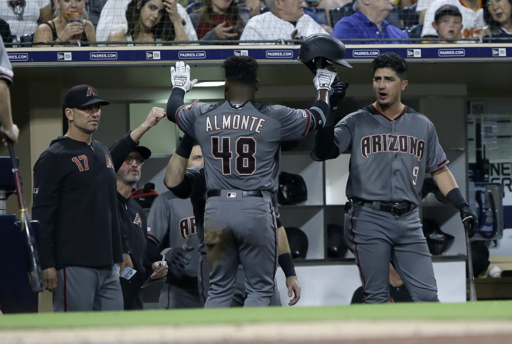 Arizona Diamondbacks' Abraham Almonte (48) gets congratulations from Josh Rojas, right, and other teammates after scoring on a fielder's choice during