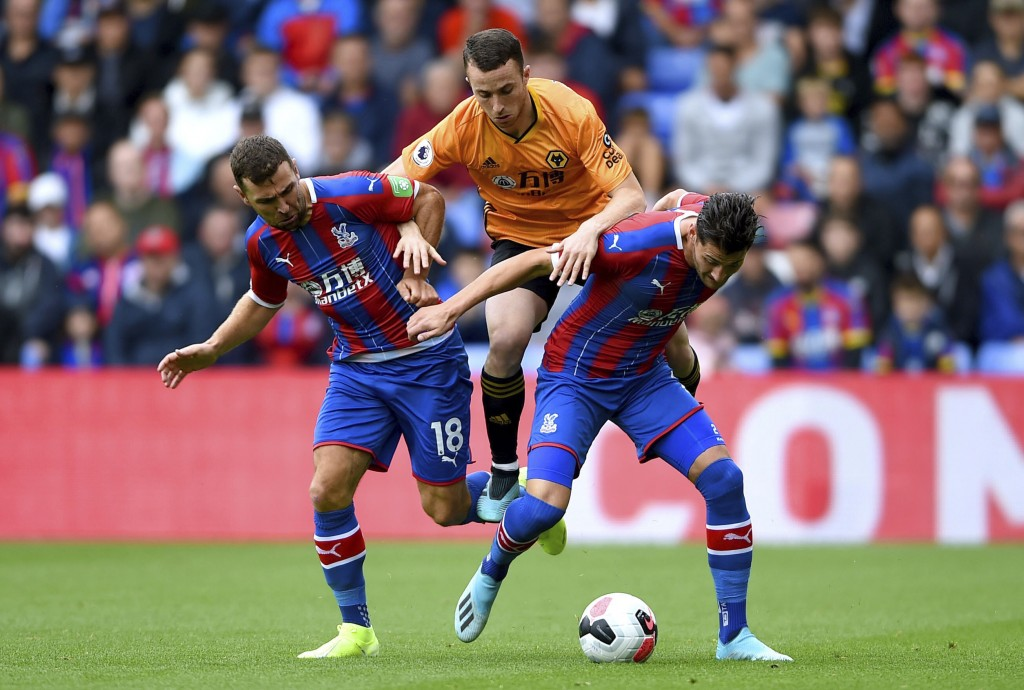Wolverhampton Wanderers' Diogo Jota, center, battles for the ball with Crystal Palace's James McArthur. left, and Joel Ward during their English Premi