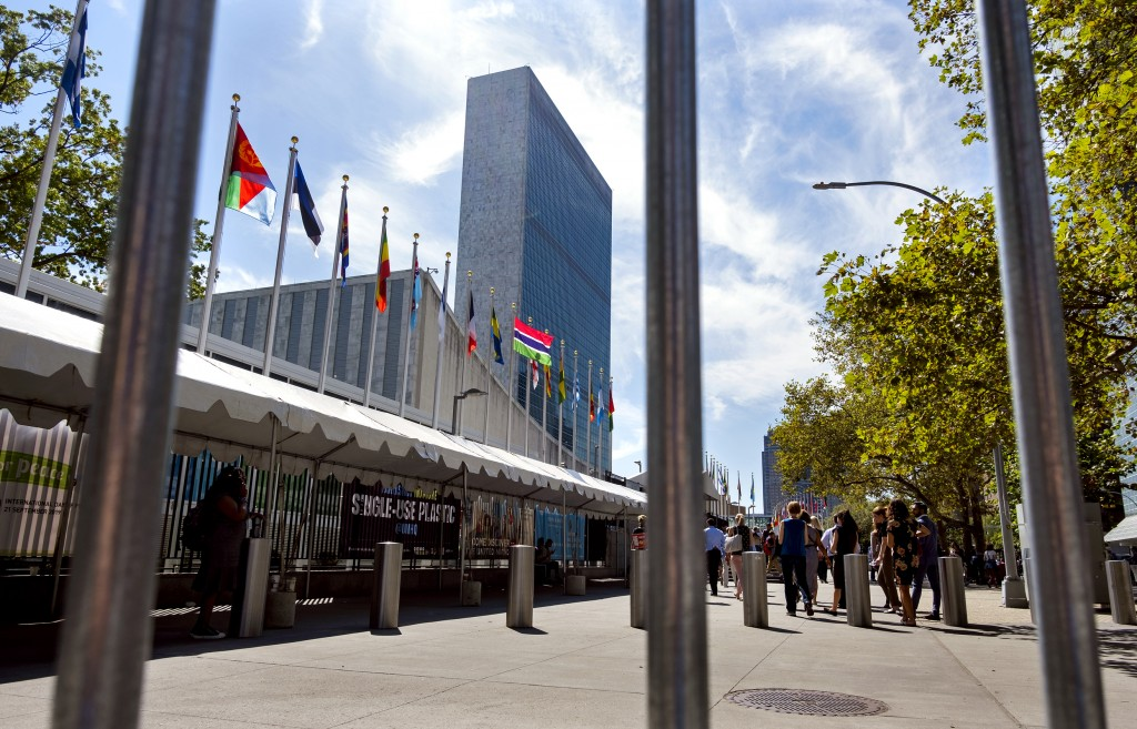 Seen tough the bars of a temporary security barrier, people walk along 1st Avenue in New York in front of United Nations Headquarters Saturday, Sept.