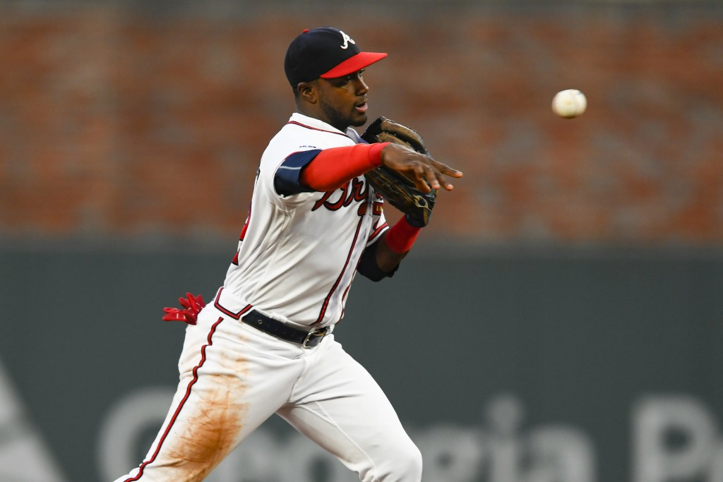 Atlanta Braves second baseman Adeiny Hechavarria throws out San Francisco Giants' Evan Longoria at first base after forcing out Buster Posey at second