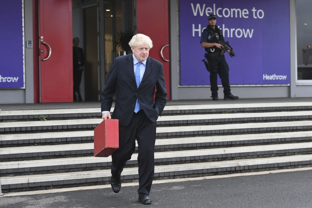 Britain's Prime Minister Boris Johnson walks to board his plane at London's Heathrow Airport as he heads off for the annual United Nations General Ass...