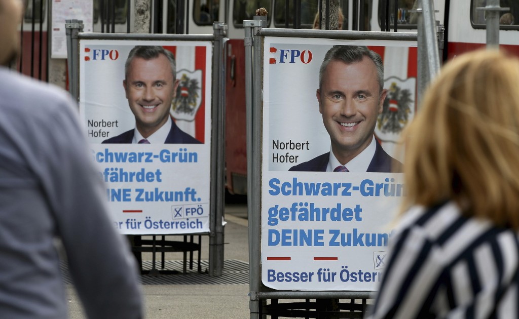 A person passes and election poster of the right-wing Freedom party, FPOE, for the upcoming Austrian national elections in Vienna, Austria, Monday, Se...