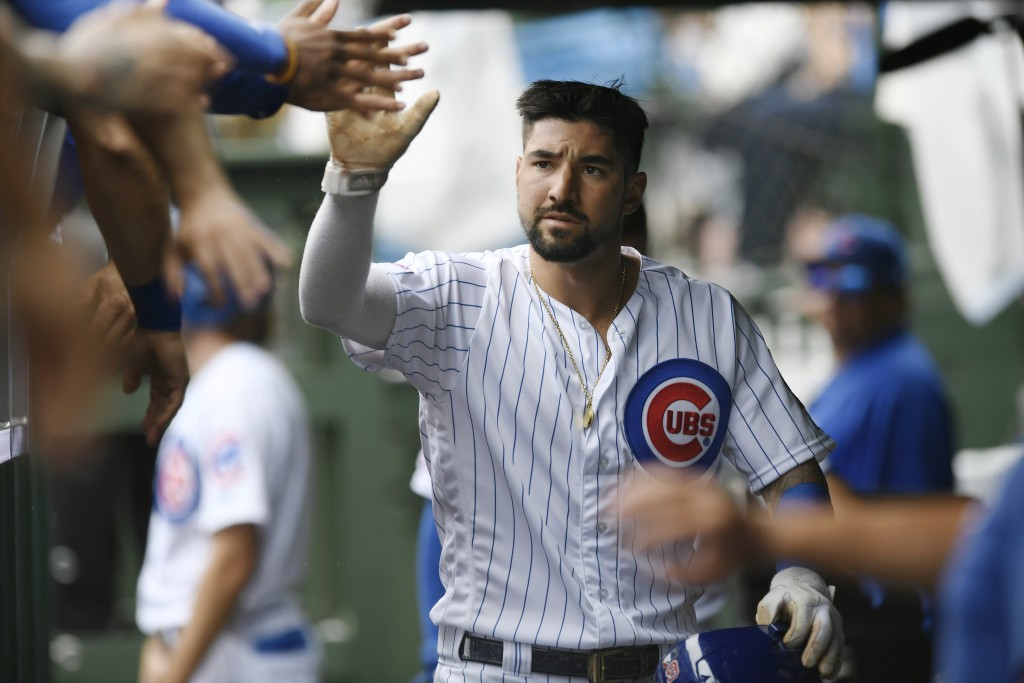 Chicago Cubs' Nicholas Castellanos celebrates with teammates in the dugout after scoring on a passed ball by St. Louis Cardinals catcher Yadier Molina...