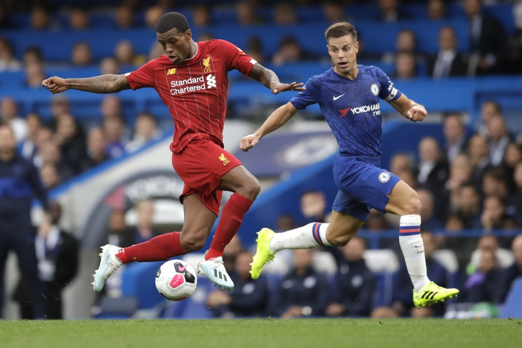 Liverpool's Georginio Wijnaldum, left, and Chelsea's Cesar Azpilicueta compete for the ball during the British premier League soccer match between Che...