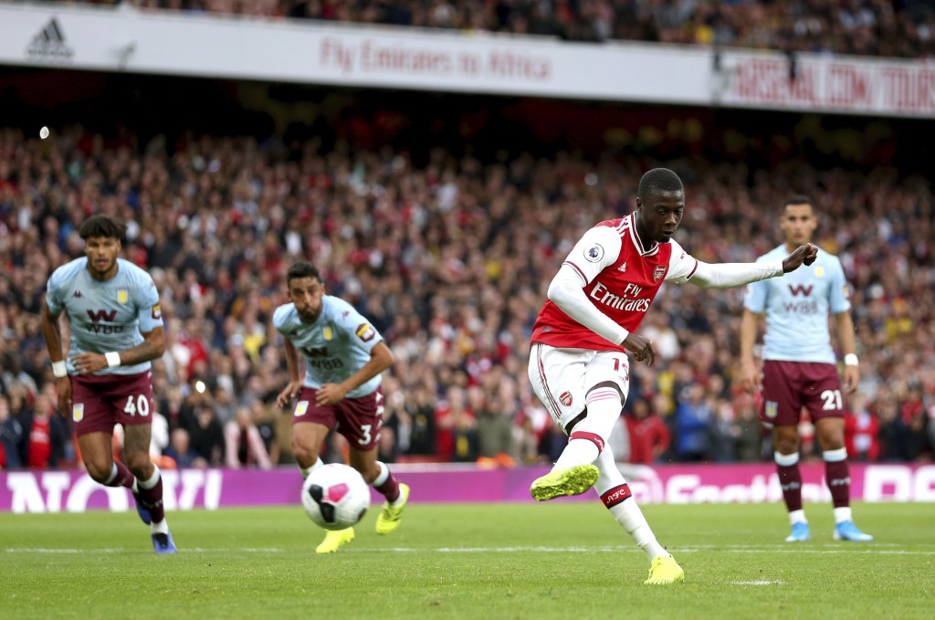 Arsenal's Nicolas Pepe, second right, scores from the penalty spot during the English Premier League soccer match at the Emirates Stadium, London, Sun