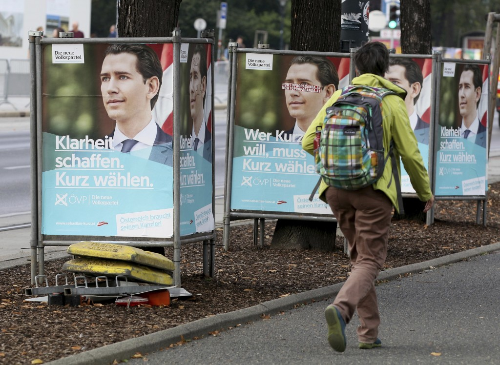 A person passes and election poster of the conservative Austrian People's Party, OEVP, with a portrait of former Austrian chancellor Sebastian Kurz, f...