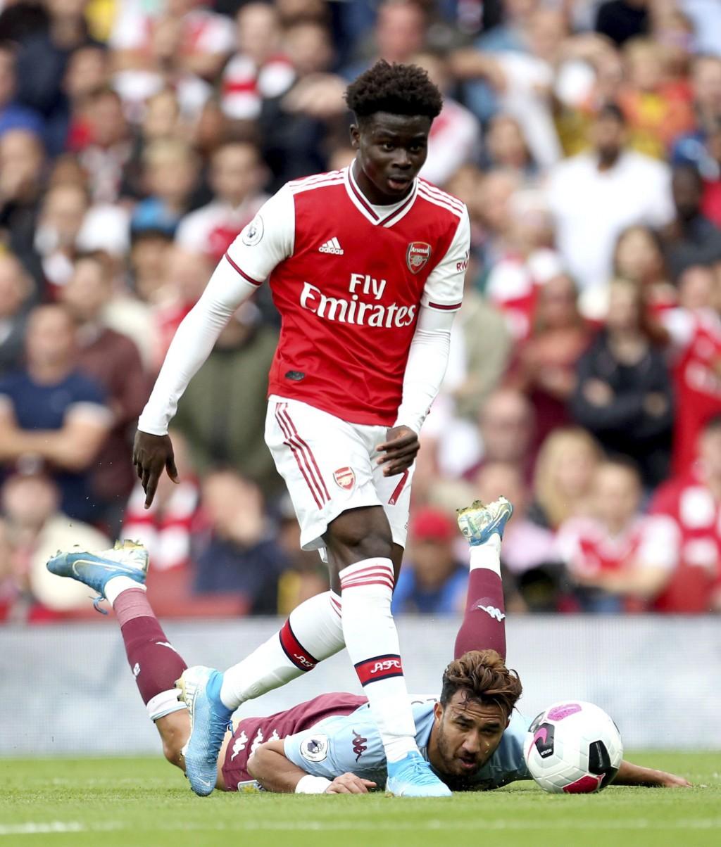 Arsenal's Bukayo Saka, top, and Aston Villa's Trezeguet battle for the ball during the Premier League match at the Emirates Stadium, London, Sunday, S...