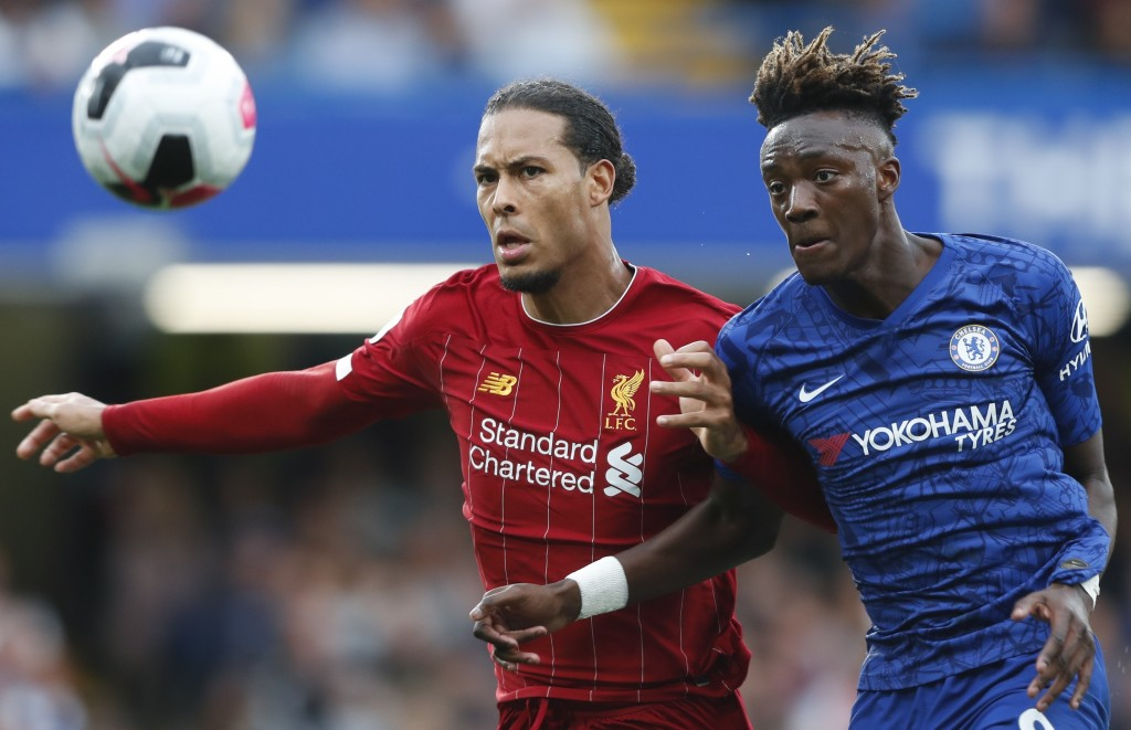 Liverpool's Virgil van Dijk, left, and Chelsea's Tammy Abraham go for the ball during the British Premier League soccer match between Chelsea and Live...