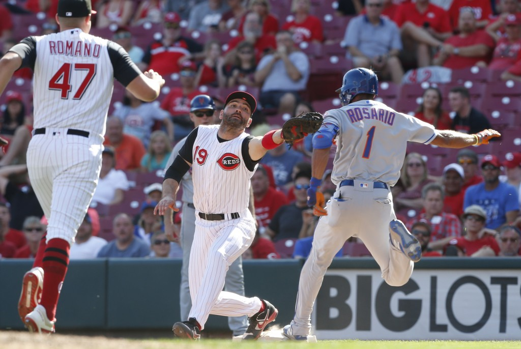 New York Mets' Amed Rosario (1) touches first base as Cincinnati Reds first baseman Joey Votto (19) takes the throw during the ninth inning of a baseb...